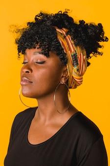 Piękna afrykańska kędzierzawa młoda kobieta na barwionym tle