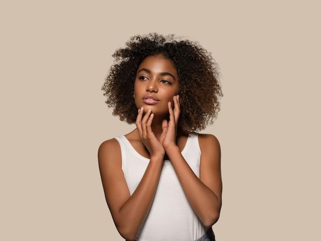 Piękna afrykańska kobieta biała koszulka portret afro fryzura dotykająca jej twarzy kolor tła brązowy