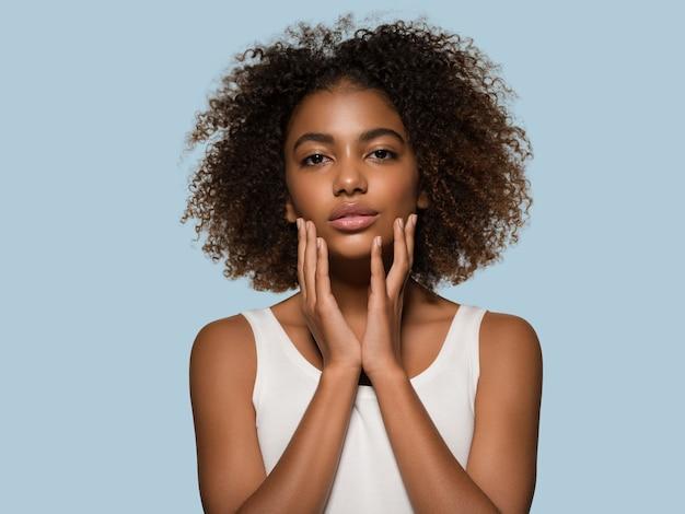 Piękna afrykańska kobieta biała koszulka portret afro fryzura dotykająca jej twarzy kolor tła niebieski