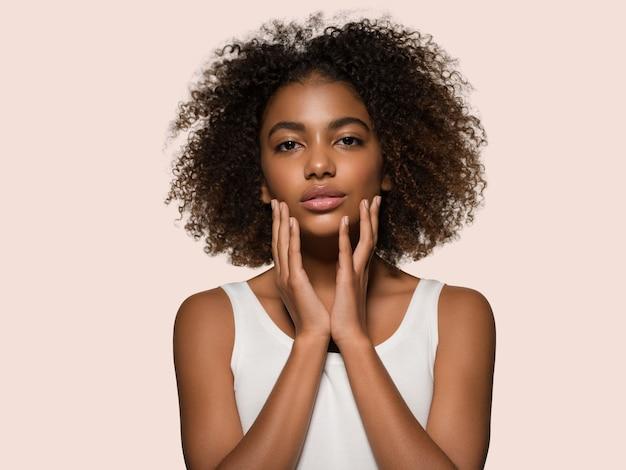 Piękna afrykańska kobieta biała koszulka portret afro fryzura dotykająca jej twarzy kolor tła różowy