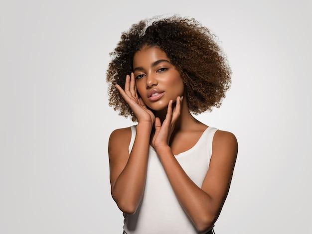 Piękna afrykańska kobieta biała koszulka portret afro fryzura dotykająca jej twarzy kolor tła szary