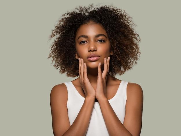 Piękna afrykańska kobieta biała koszulka portret afro fryzura dotykająca jej twarzy kolor tła zielony