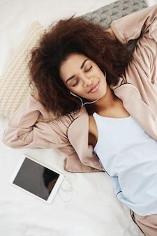 Piękna afrykańska kobieta ono uśmiecha się w bielizna nocna słucha muzyka w hełmofonach kłama na łóżku.
