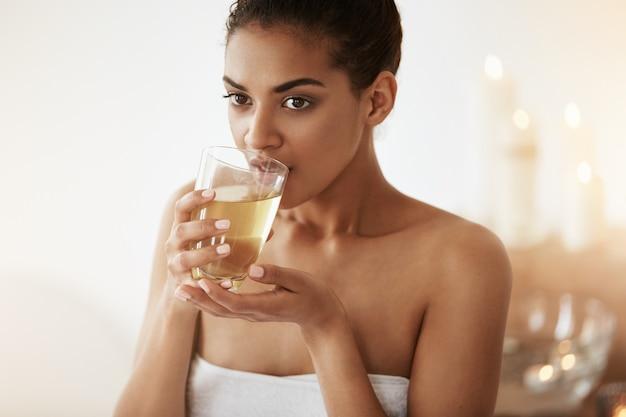 Piękna afrykańska kobieta pije herbaciany ono uśmiecha się relaksować w zdroju salonie.