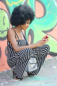 Piękna afrykańska kobieta przy użyciu telefonu komórkowego na ulicy