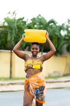 Piękna afrykańska kobieta trzymająca odbiorcę wody