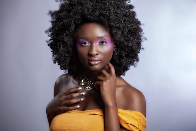 Piękna afrykańska kobieta z dużym kręconym afro i kwiatami we włosach