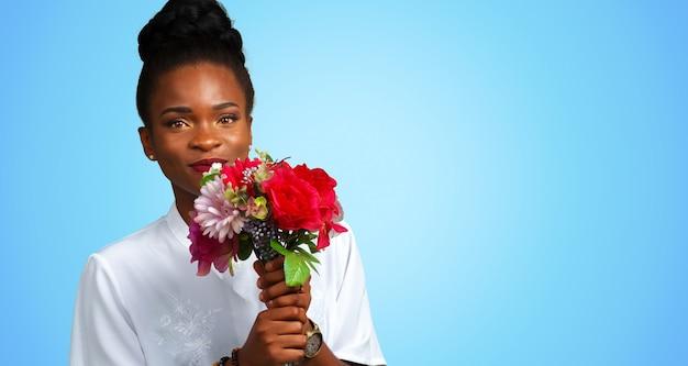 Piękna afrykańska kobieta ze świeżymi kolorowymi kwiatami