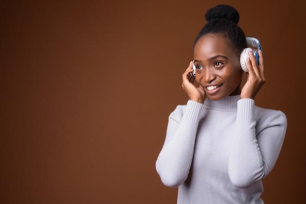 Piękna afrykańska kobieta zulu słuchania muzyki za pomocą słuchawek