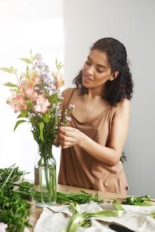 Piękna afrykańska żeńska kwiaciarnia ono uśmiecha się robić bukietowi kwiaty.