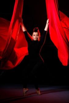 Piękna akrobatka sportive wykonuje ćwiczenia gimnastyczne i cyrkowe na czerwonym jedwabiu. gimnastyka powietrzna na płótnie