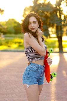 Piękna aktywna brunetka dziewczyna z długimi włosami na sobie top, niebieskie dżinsowe szorty i stylowe różowe trampki pozowanie na tle zachodu słońca. trzymając pomarańczową łyżwę z zielonymi kołami.