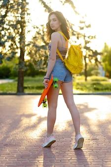 Piękna aktywna brunetka dziewczyna z noszeniem top, niebieskie dżinsowe szorty i stylowe różowe trampki pozowanie na tle zachodu słońca. dziewczyna trzyma pomarańczową łyżwę z zielonymi kołami. dziewczyna stoi plecami