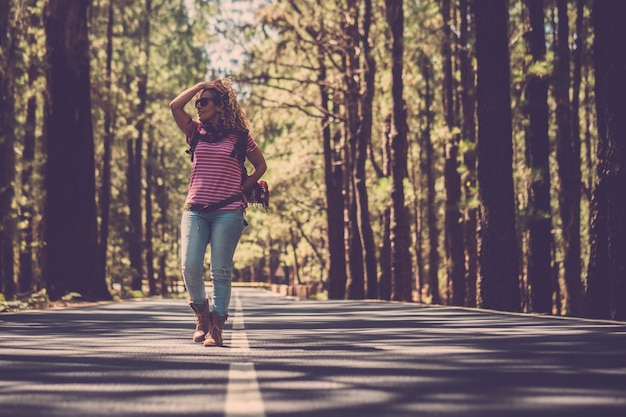Piękna alternatywna kobieta, która spaceruje pośrodku drogi w wysokim lesie sosnowym w lesie, aby podróżować przygodą anejoy, podróżować samotnie w kontakcie i czuć się na świeżym powietrzu