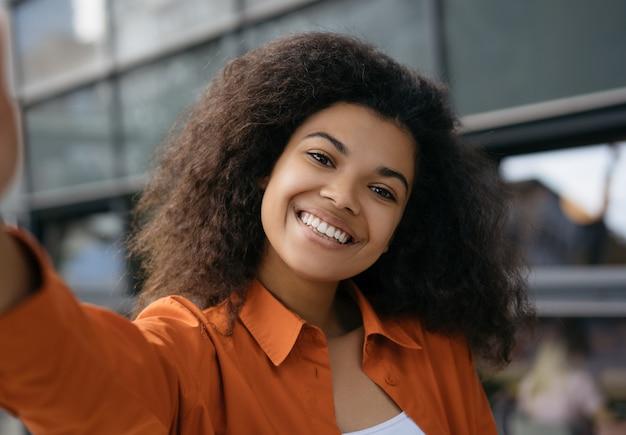 Piękna amerykanin afrykańskiego pochodzenia kobieta bierze selfie na telefonie komórkowym. blogger streaming wideo online