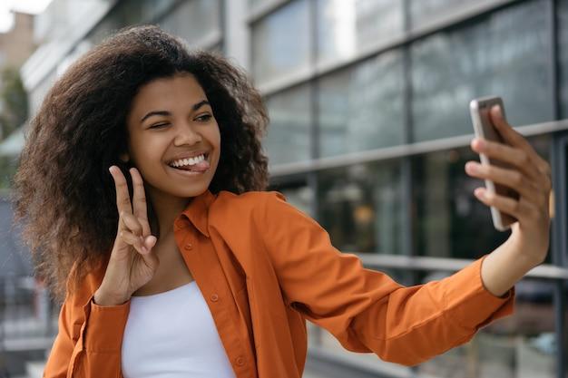 Piękna amerykanin afrykańskiego pochodzenia kobieta bierze selfie na telefonie komórkowym, pokazuje zwycięstwo znaka. blogger streaming wideo online