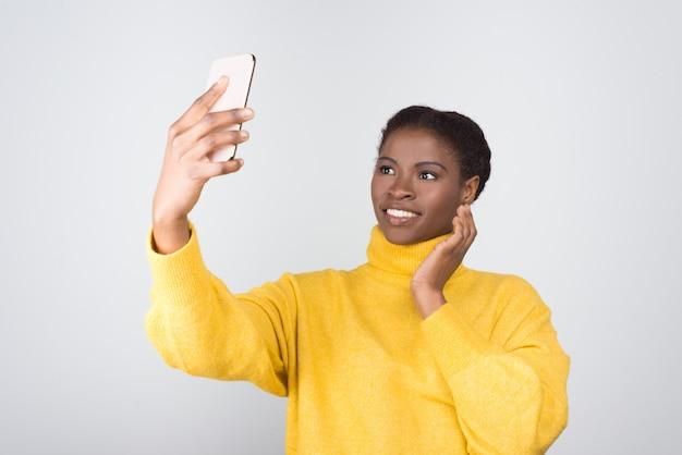 Piękna amerykanin afrykańskiego pochodzenia kobieta bierze selfie z smartphone