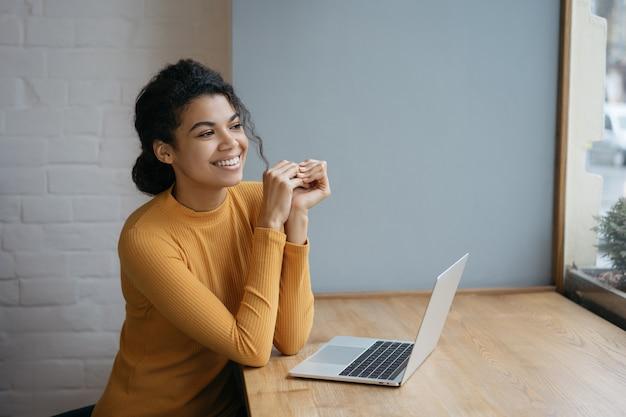 Piękna amerykanin afrykańskiego pochodzenia kobieta siedzi w kawiarni, uśmiecha się, patrzeje przez okno, czeka taxi