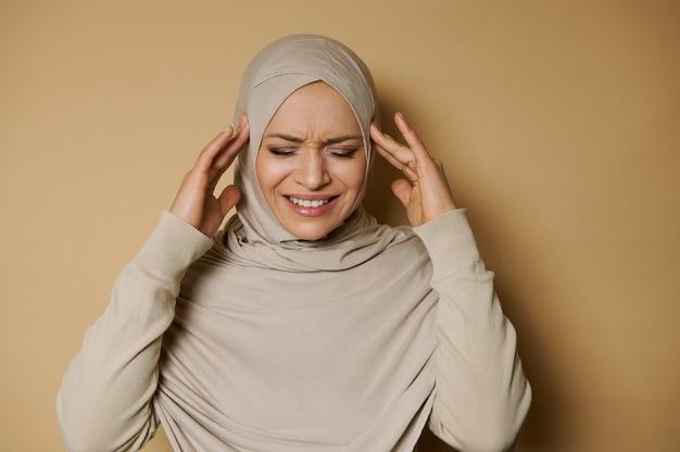 Piękna arabka w hidżabie pozuje do przodu wyrażając ból i ból głowy na beżowej powierzchni z miejsca na kopię