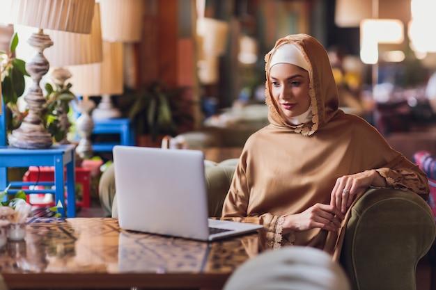 Piękna arabska biznesowa kobieta pracuje na komputerze.