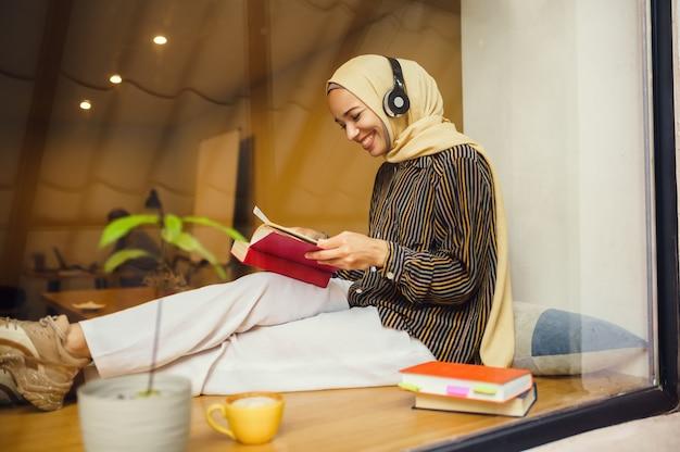 Piękna arabska dziewczyna w hidżabie i słuchawkach w kawiarni uniwersyteckiej. muzułmanka z książkami siedzi w bibliotece.