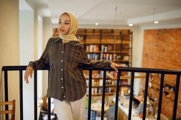 Piękna arabska dziewczyna w pozach hidżabu w kawiarni uniwersyteckiej. muzułmanka z książkami siedzi w bibliotece.