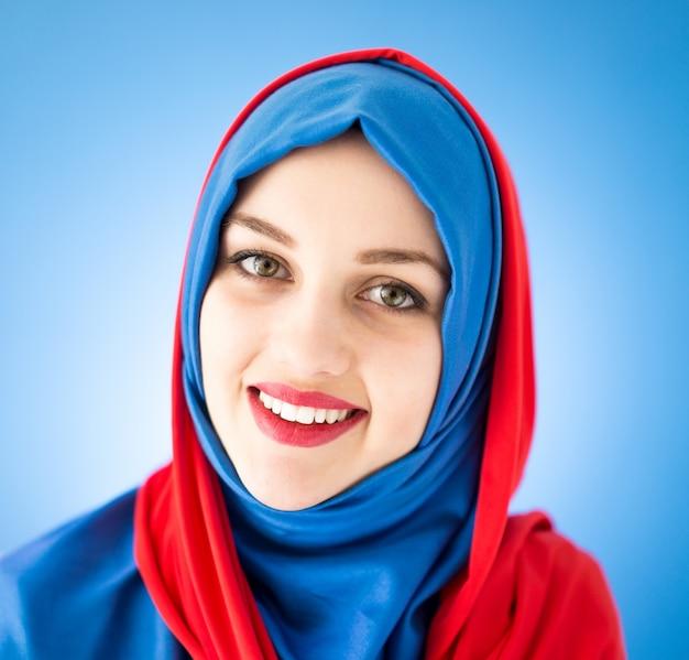 Piękna arabska dziewczyna z szalikiem nad błękitnym tłem
