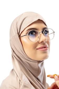 Piękna arabska kobieta pozuje w stylowym hidżabie na białym tle na koncepcji mody