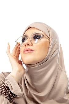 Piękna arabska kobieta pozuje w stylowym hidżabie na tle koncepcji mody w studio