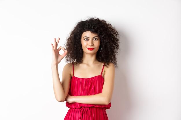Piękna asertywna kobieta z kręconymi fryzurami i makijażem, ubrana w czerwoną sukienkę, pokazująca dobry znak i uśmiechająca się z aprobatą, mówi tak, stojąc na białym tle.