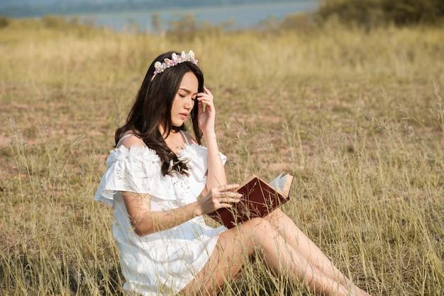 Piękna asia dziewczyna czyta książkę zakrywającą przy trawy polem