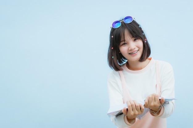 Piękna asia kobieta, nastoletnia dziewczyna czytelnicza książka z szczęśliwym w czasie wolnym, wakacje.