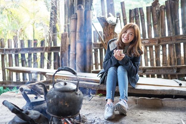 Piękna asia kobieta trzyma filiżankę i obsiadanie na drewnianym pobliskim czajniku na ogieniu.