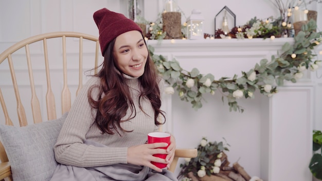 Piękna atrakcyjna azjatycka kobieta trzyma ciepłą filiżankę kawy lub herbaty podczas gdy kłamający na krześle