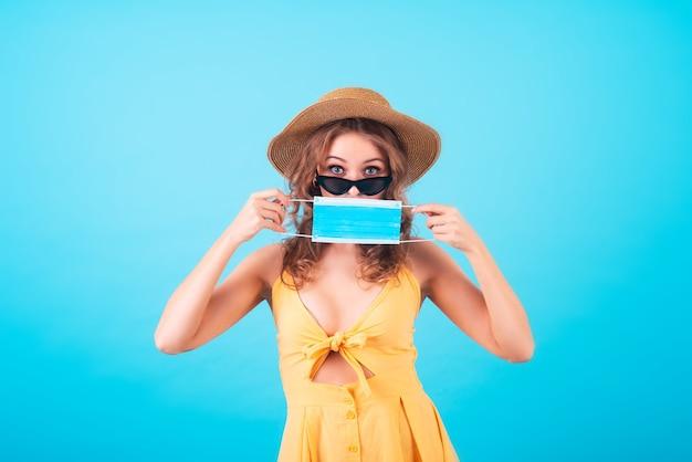 Piękna, atrakcyjna europejka w modnej żółtej sukience, okularach przeciwsłonecznych i słomkowym kapeluszu zakrywa twarz medyczną maską na niebieskim tle. kopiuj przestrzeń, podróżuj w warunkach pandemii