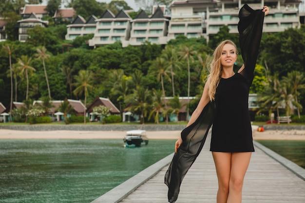 Piękna atrakcyjna kobieta ubrana w czarną sukienkę pozowanie na molo w luksusowym hotelu, wakacje, tropikalna plaża