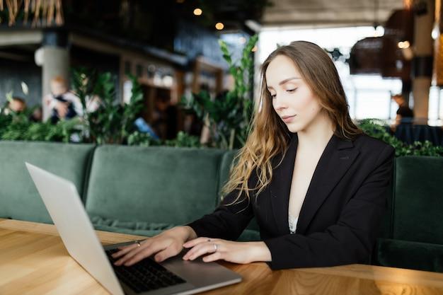 Piękna atrakcyjna kobieta w kawiarni z laptopem po przerwie na kawę