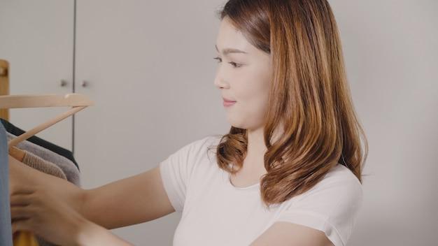 Piękna atrakcyjna młoda azjatycka kobieta wybiera jej moda strój odziewa w szafie w domu