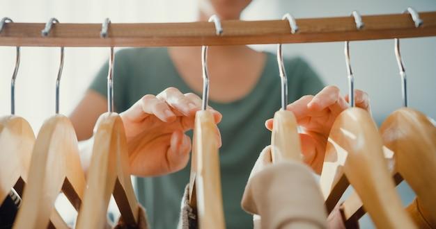 Piękna atrakcyjna młoda dama azji wybierając jej strój mody ubrania w salonie szafie w domu lub sklepie. dziewczyna pomyśl, w co się ubrać casualową koszulę