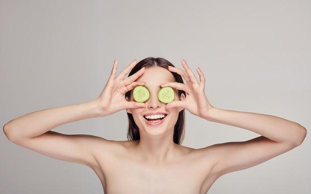 Piękna atrakcyjna młoda dama z włosami z pełnymi ustami i zabawnym nastrojem. kobieta zrobiła okulary z kawałków ogórka i uśmiechała się białymi zębami. spa, kosmetyki. środkowa rama
