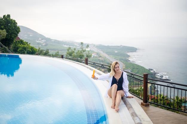 Piękna atrakcyjna młoda kobieta siedzi w pobliżu dużego basenu z widokiem na morze. koncepcja wakacji. dziewczyna w czarnym kostiumie kąpielowym smaruje skórę kremem przeciwsłonecznym