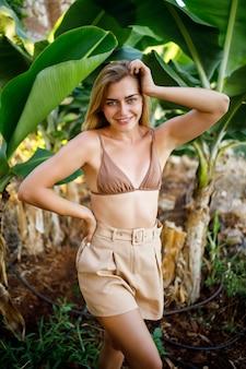 Piękna atrakcyjna młoda kobieta stoi w pobliżu drzewa bananowego, dziewczyna ubrana w strój kąpielowy spaceruje po plantacji bananów, egzotyczne rośliny