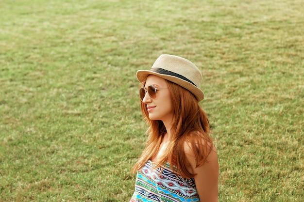 Piękna atrakcyjna młoda kobieta uśmiecha się i cieszy w parku z kapeluszem.
