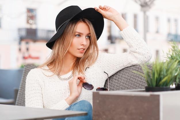Piękna atrakcyjna młoda kobieta w biały sweter z dzianiny w dżinsach w stylowym eleganckim kapeluszu siedzi na kanapie przy szarym stole w ulicznej kawiarni w ciepły słoneczny dzień. europejski blond dziewczyna.