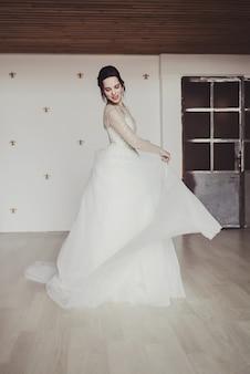 Piękna atrakcyjna panna młoda w sukni ślubnej z długą pełną spódnicą, tańcem i uśmiechem