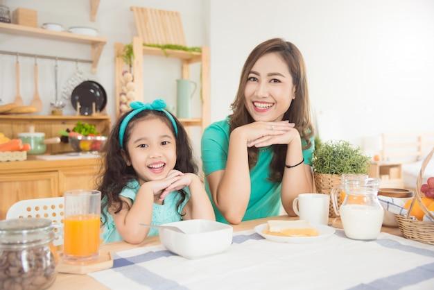 Piękna azjata matka, córka ma śniadanie w domu wpólnie w ranku i