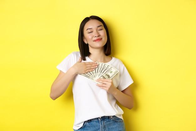 Piękna azjatka kocha pieniądze, ściska dolary i uśmiecha się zadowolony, stojąc nad żółtym.