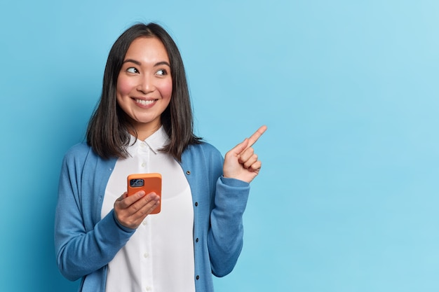 Piękna azjatka korzysta z aplikacji na smartfona, wysyła wiadomości na czacie w mediach społecznościowych, oddalając się od miejsca kopiowania, nosi swobodny sweter