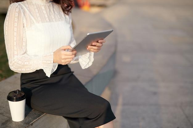 Piękna azjatka, korzystająca z komputera typu tablet na świeżym powietrzu w mieście, aby zakończyć własny biznes