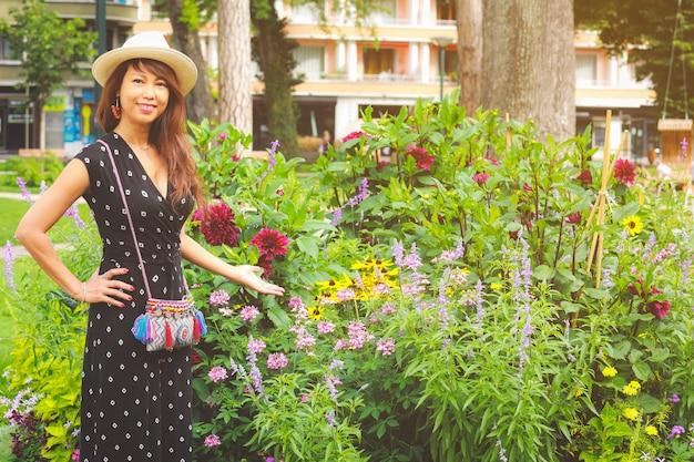 Piękna azjatka, która latem stoi w pobliżu drzewa z kolorowymi kwiatami